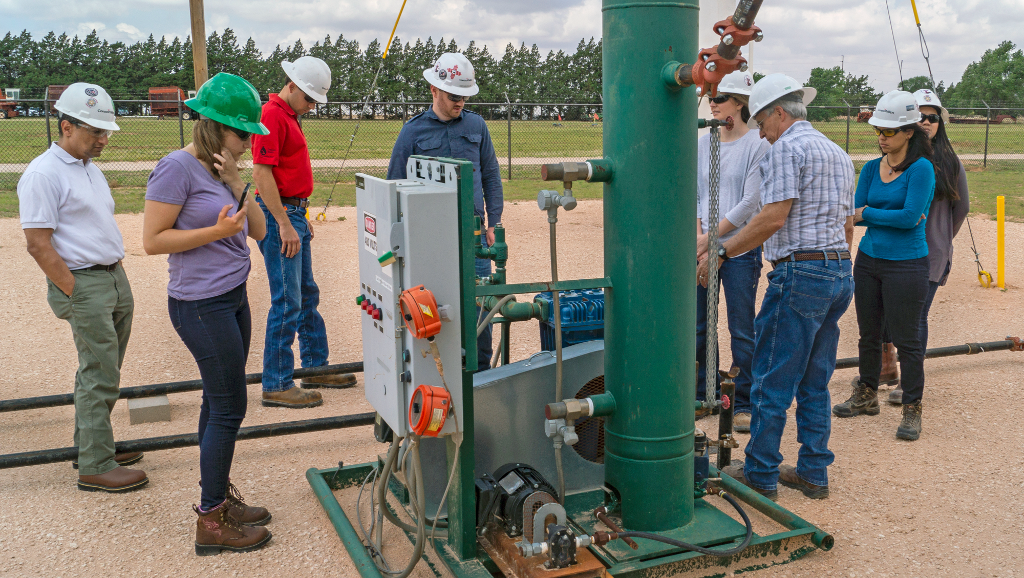 Group of people gathered around outdoor well site equipment