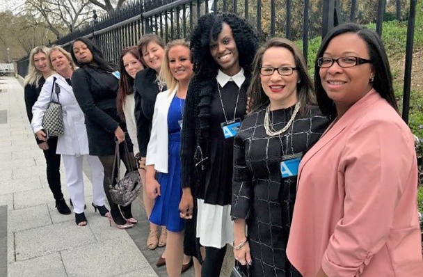 nine women in line along fence at White House