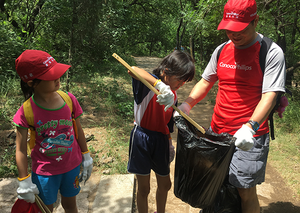 2 children and an adult collect trash