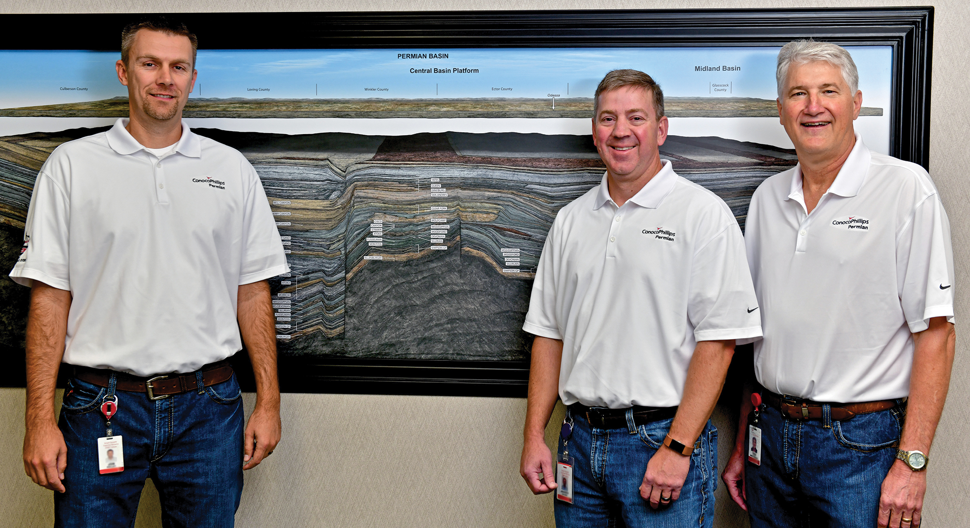 three men standing in front of cross section picture