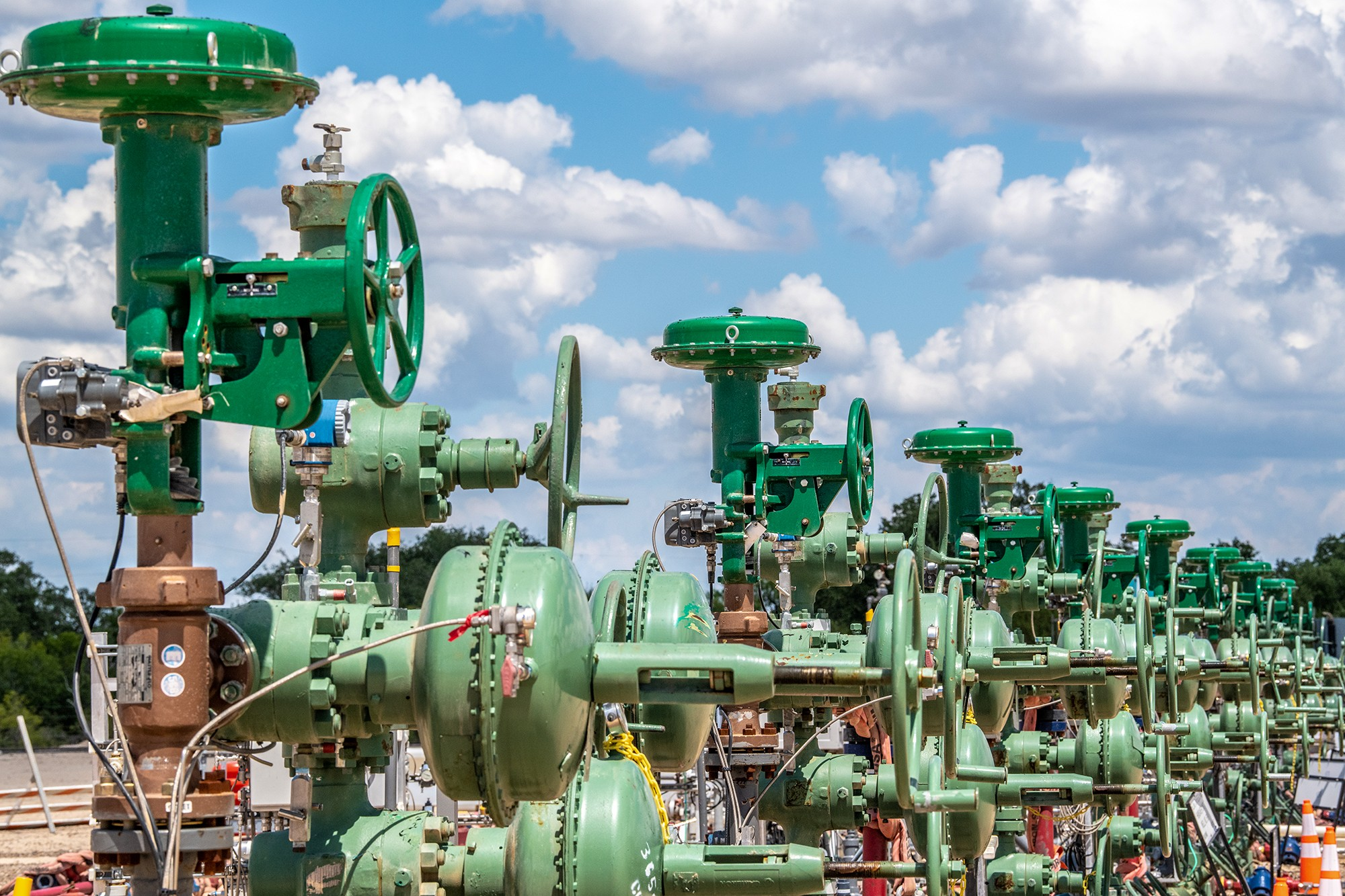 A line of wellheads with a background of blue sky and fluffy clouds