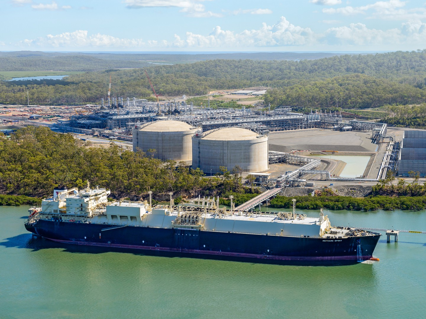 LNG ship at dock in foreground with tanks and facility in background surrounded by trees.