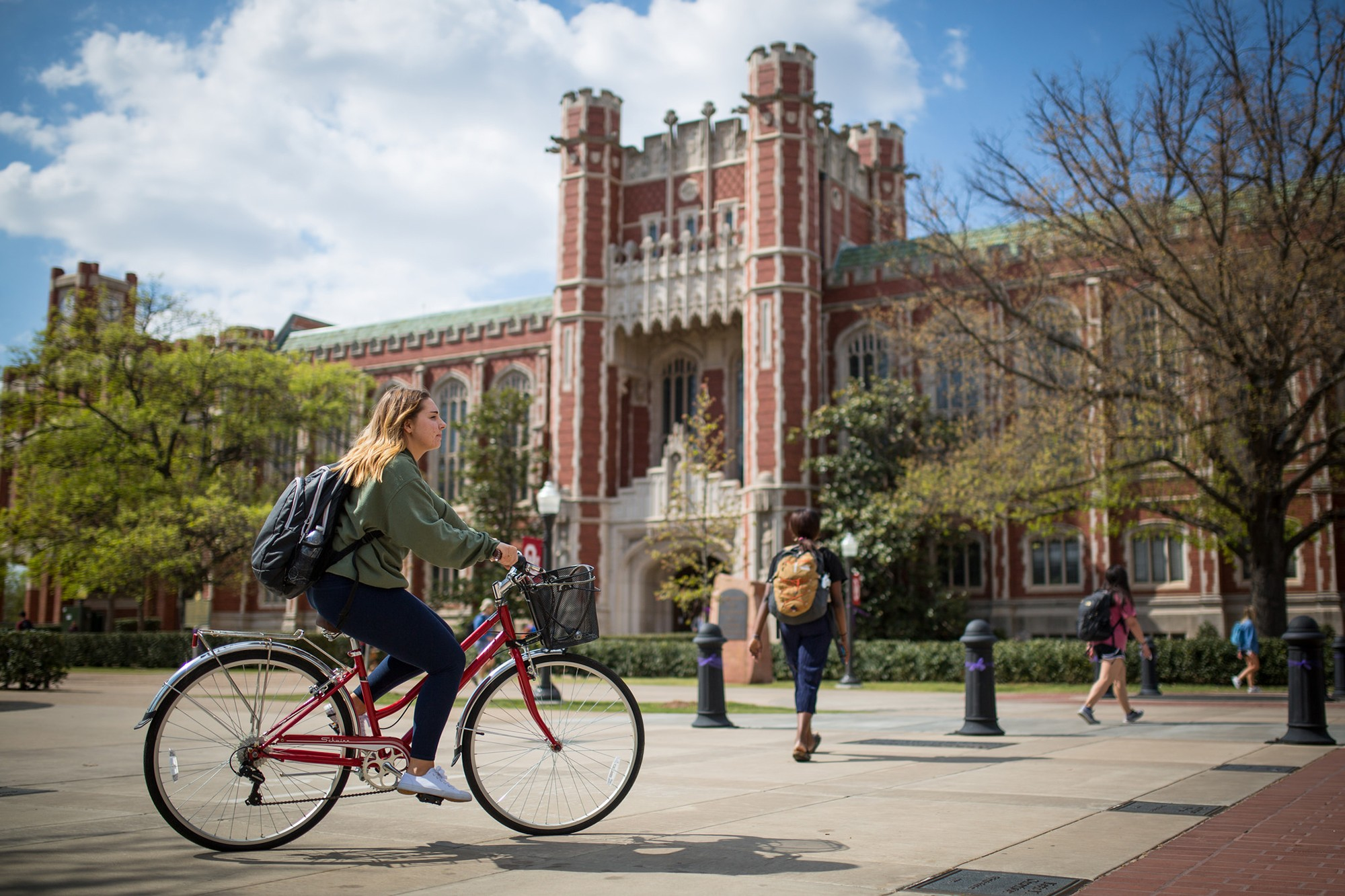 University of Oklahoma building in background with people walking outside, girl on bicycle in foreground