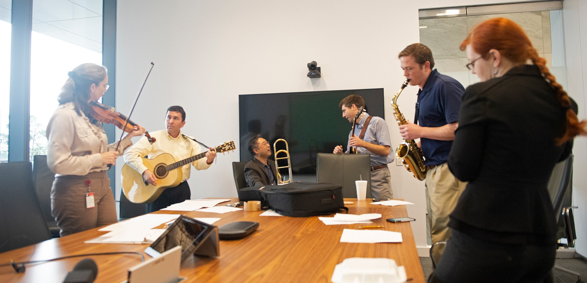 employees gathered around conference table holding instruments and reading music