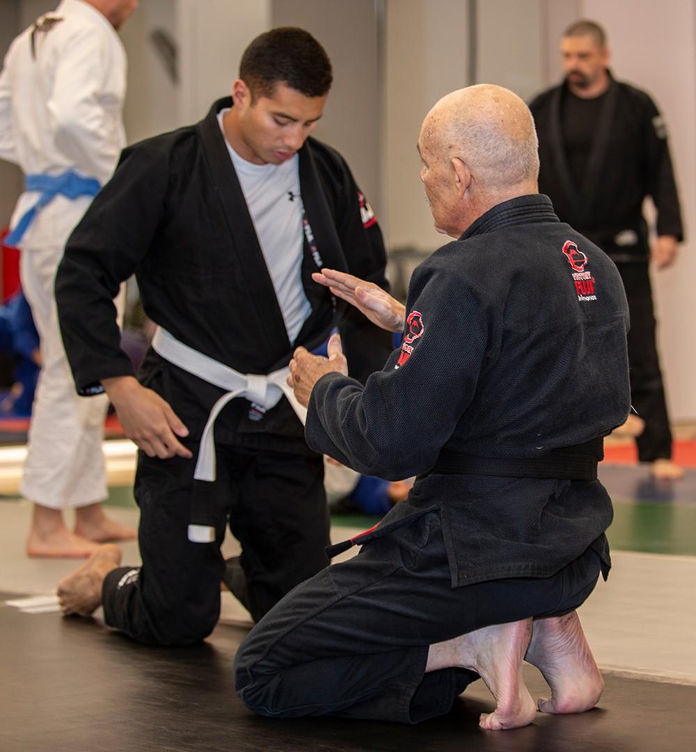 Two men kneeling in jiu jitsu attire on mat