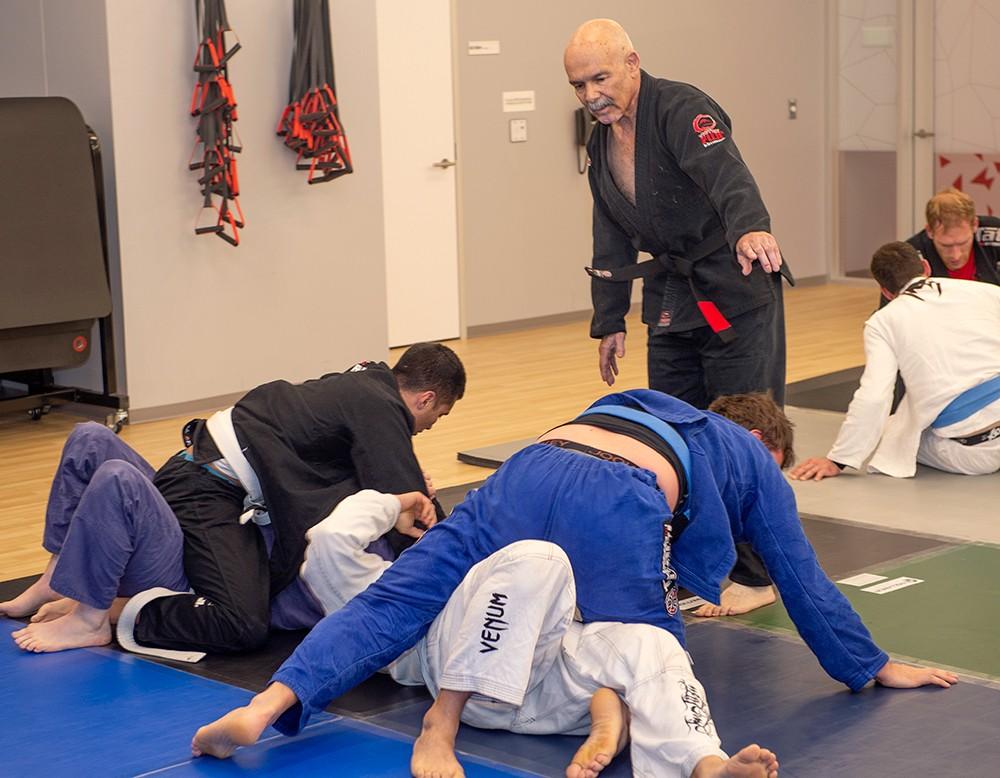 Luis instructing four men on mat