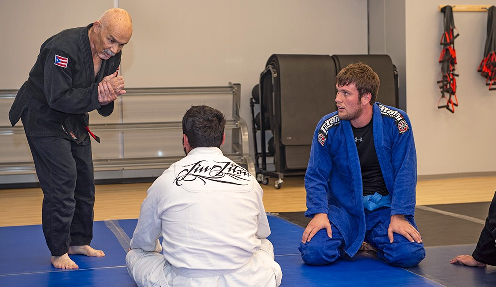 Luis instructing 2 men kneeling on mat