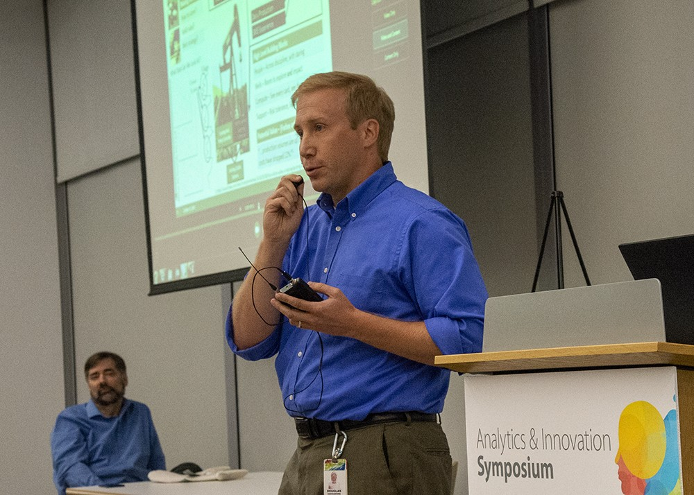 Doug Hakkarinen standing beside podium with presentation screen behind