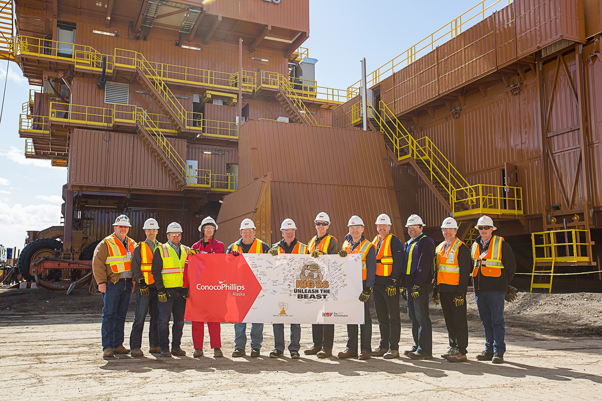 Group of 12 workers in front of rig holding banner
