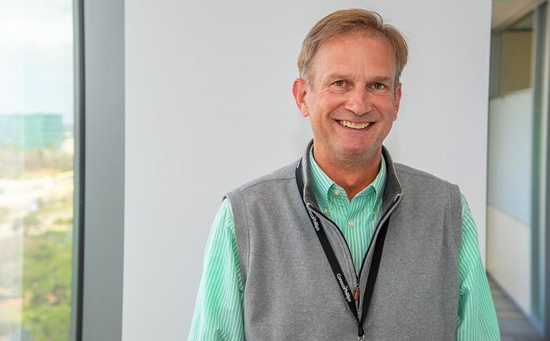Craig Dunagan smiling, standing near tall windows
