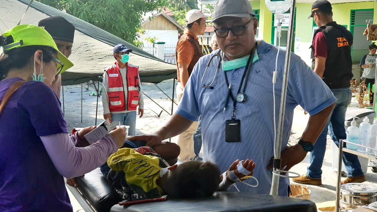 Dr. Ary Soeharijanto and nurse helping child on stretcher. Building, tent, and people in background