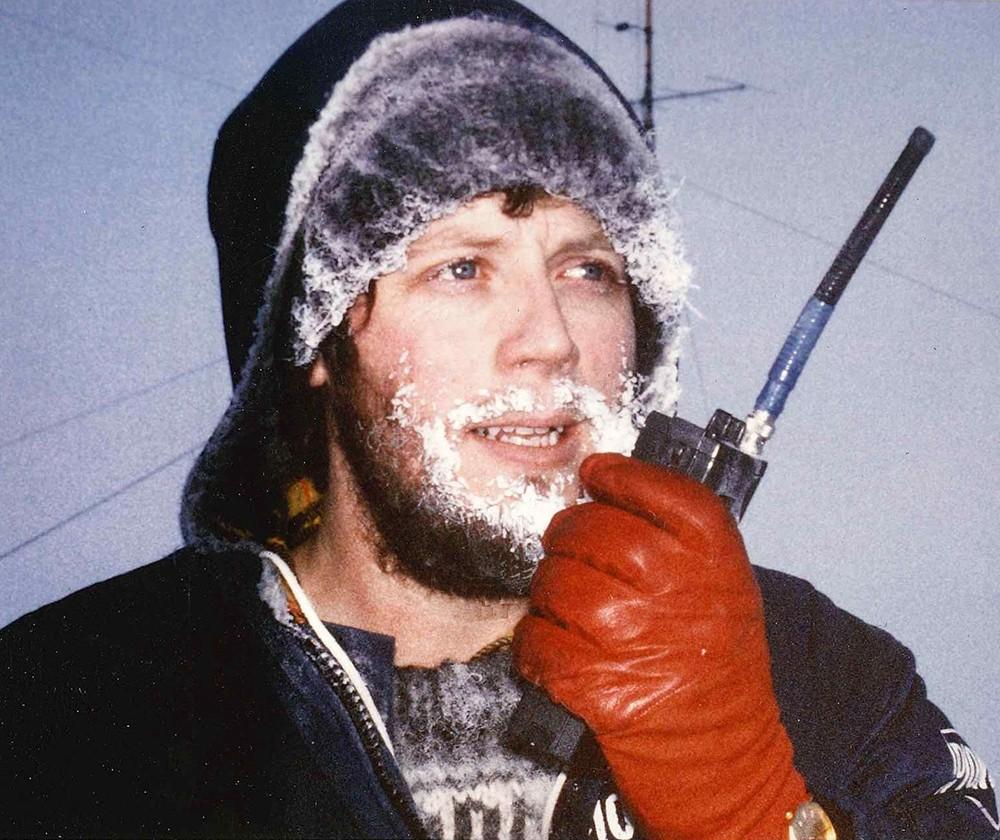 Laurence Howell with snow encrusted beard speaking into Walkie Talkie