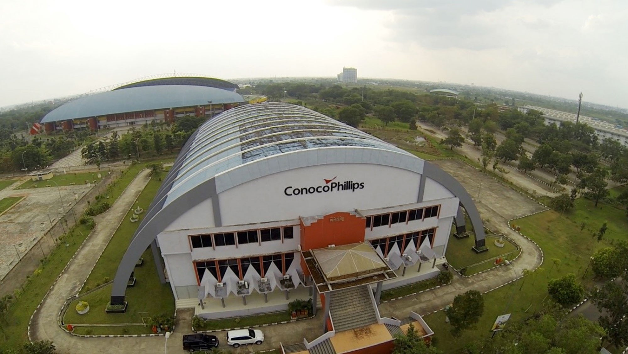 Aerial view of sports hall with curved roof and ConocoPhillips logo above entrance