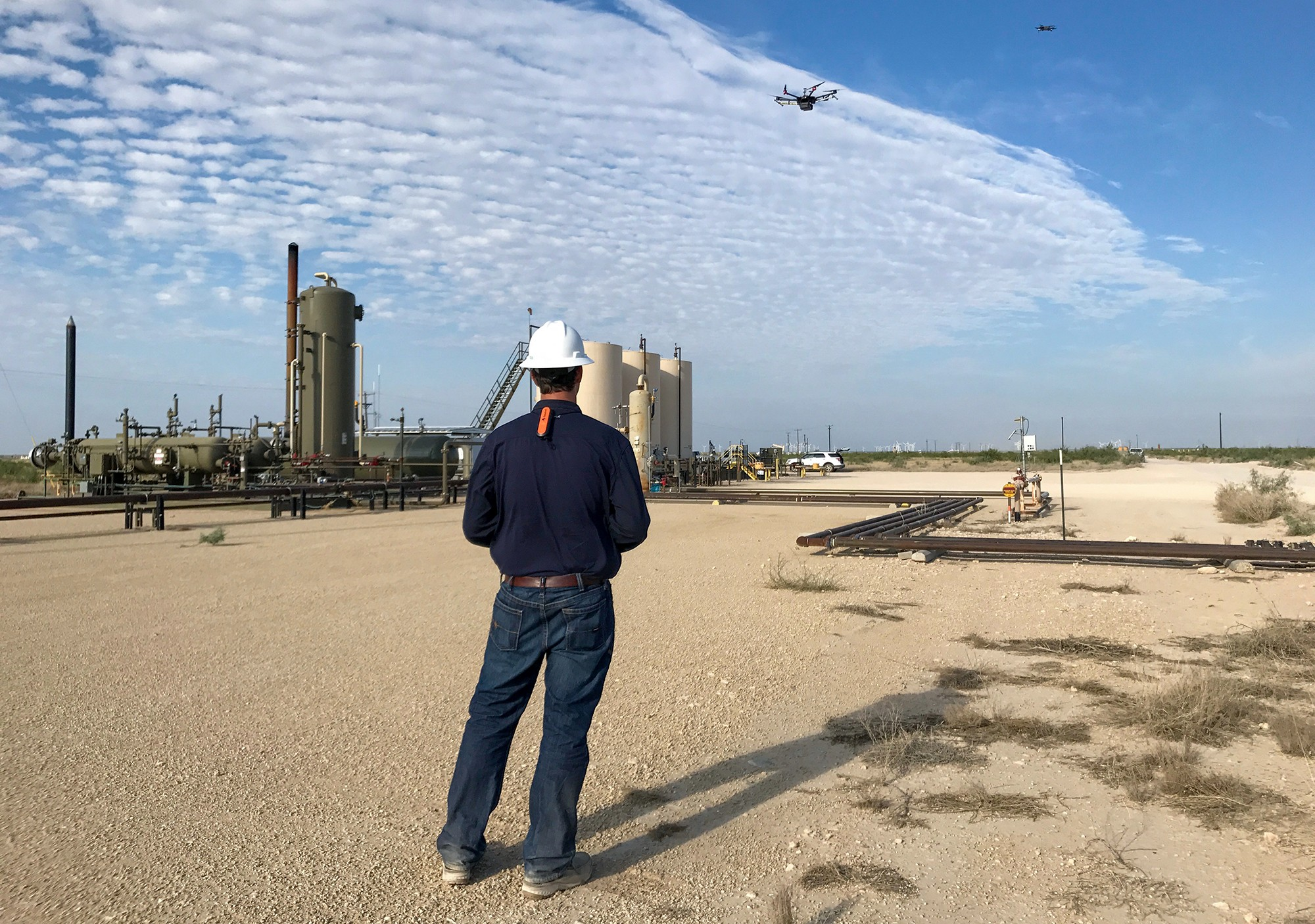 Worker wearing hardhat operating drone with tanks in background