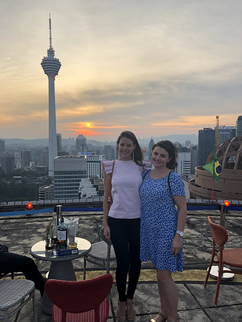 Two women on rooftop with city and sunset in background