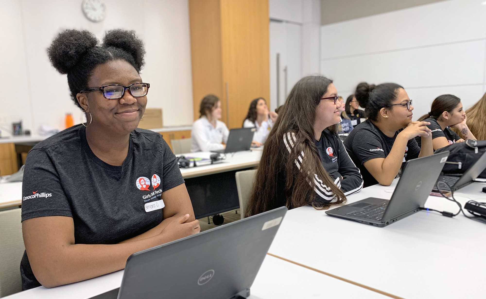 smiling student in foreground with laptop