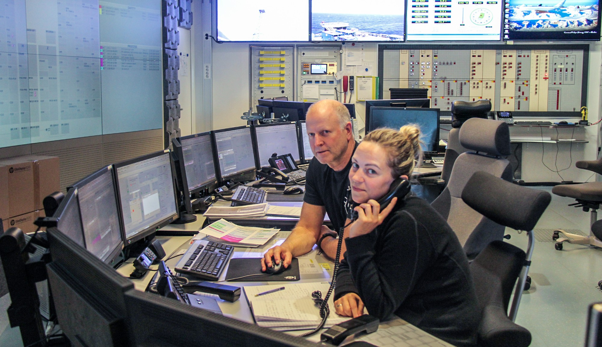 Two people at desk in control room surrounded by computer screens