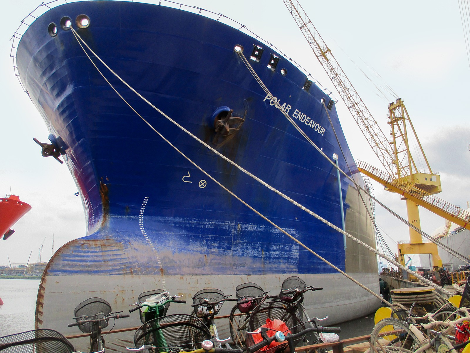 view of ship's bow looking upward from dock, bicycles parked in foreground