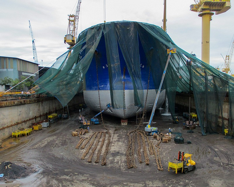 ship's bow in dry dock with cranes surrounding