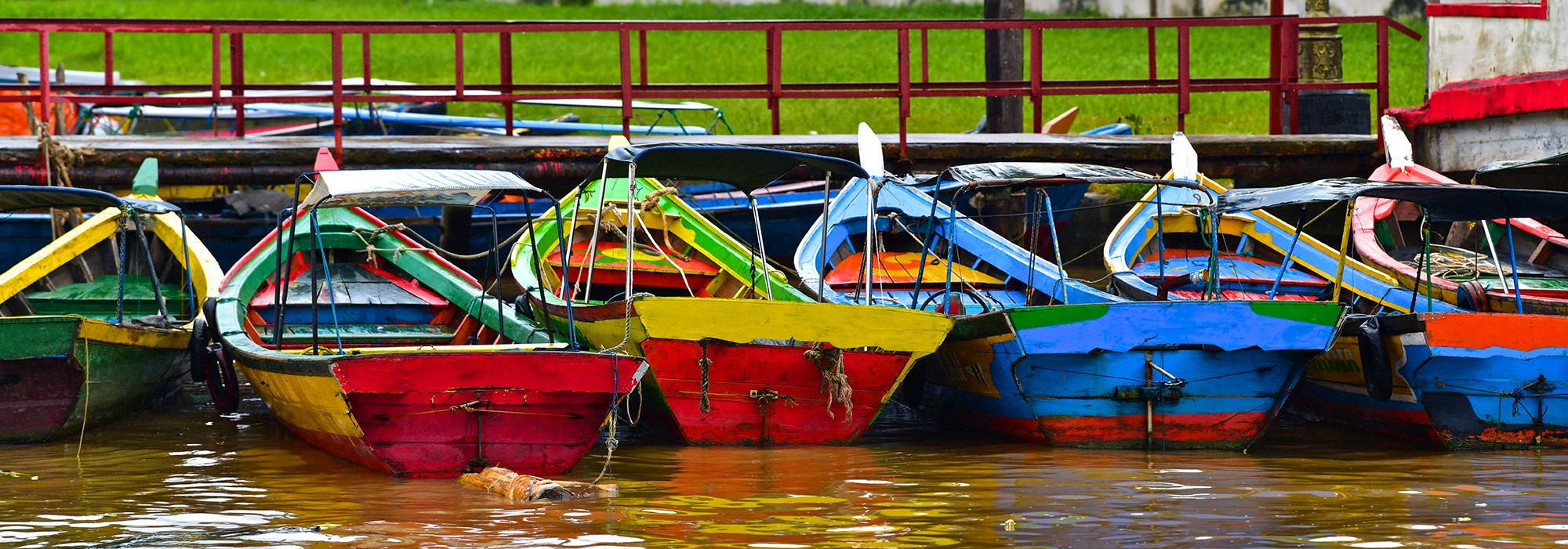 Brightly painted wooden boats tied to dock