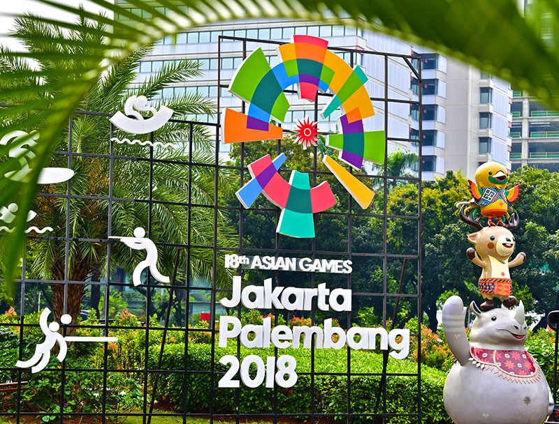 Outdoor sign with people icons and text: 18th Asian Games, Jakarta Palembang 2018