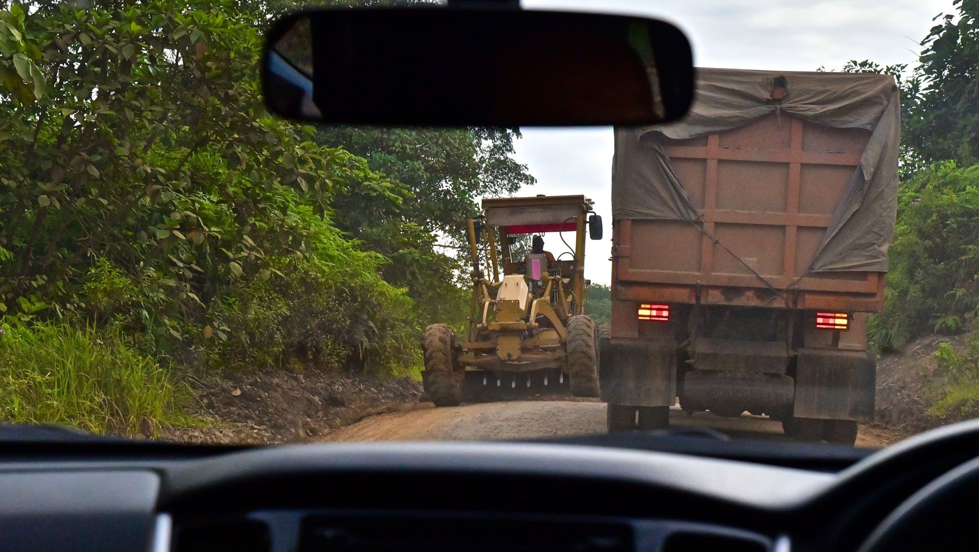 View from car windshield of road with truck and tractor