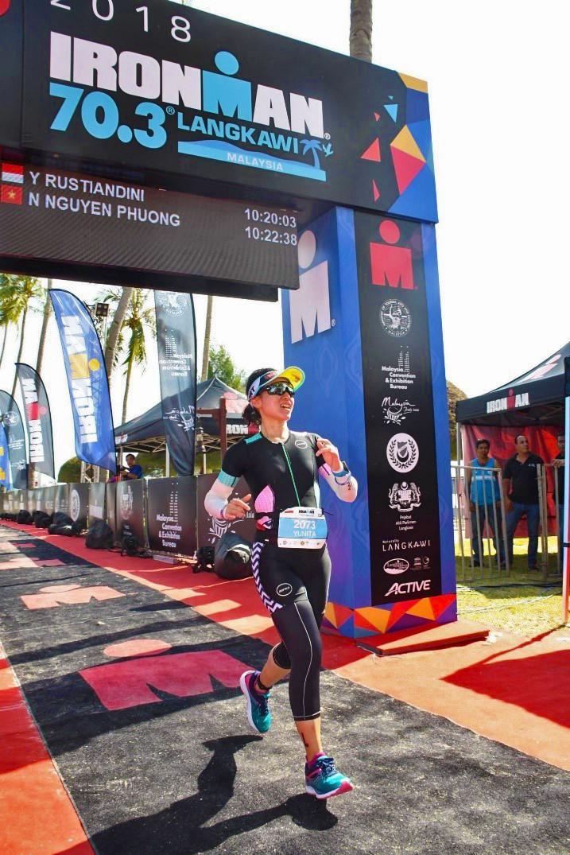 women jogging through Ironman finish line