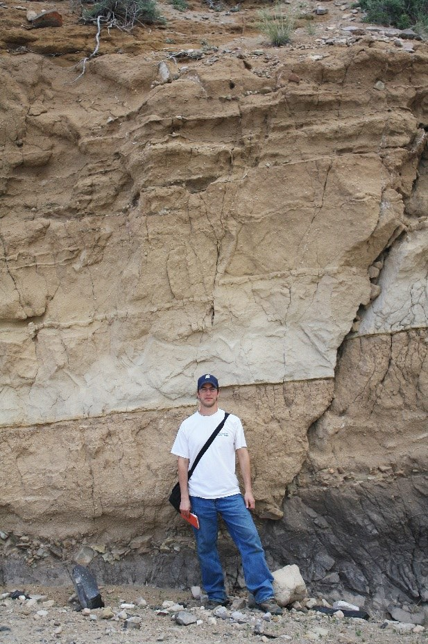 Jason in front of wall of sedimentary rock