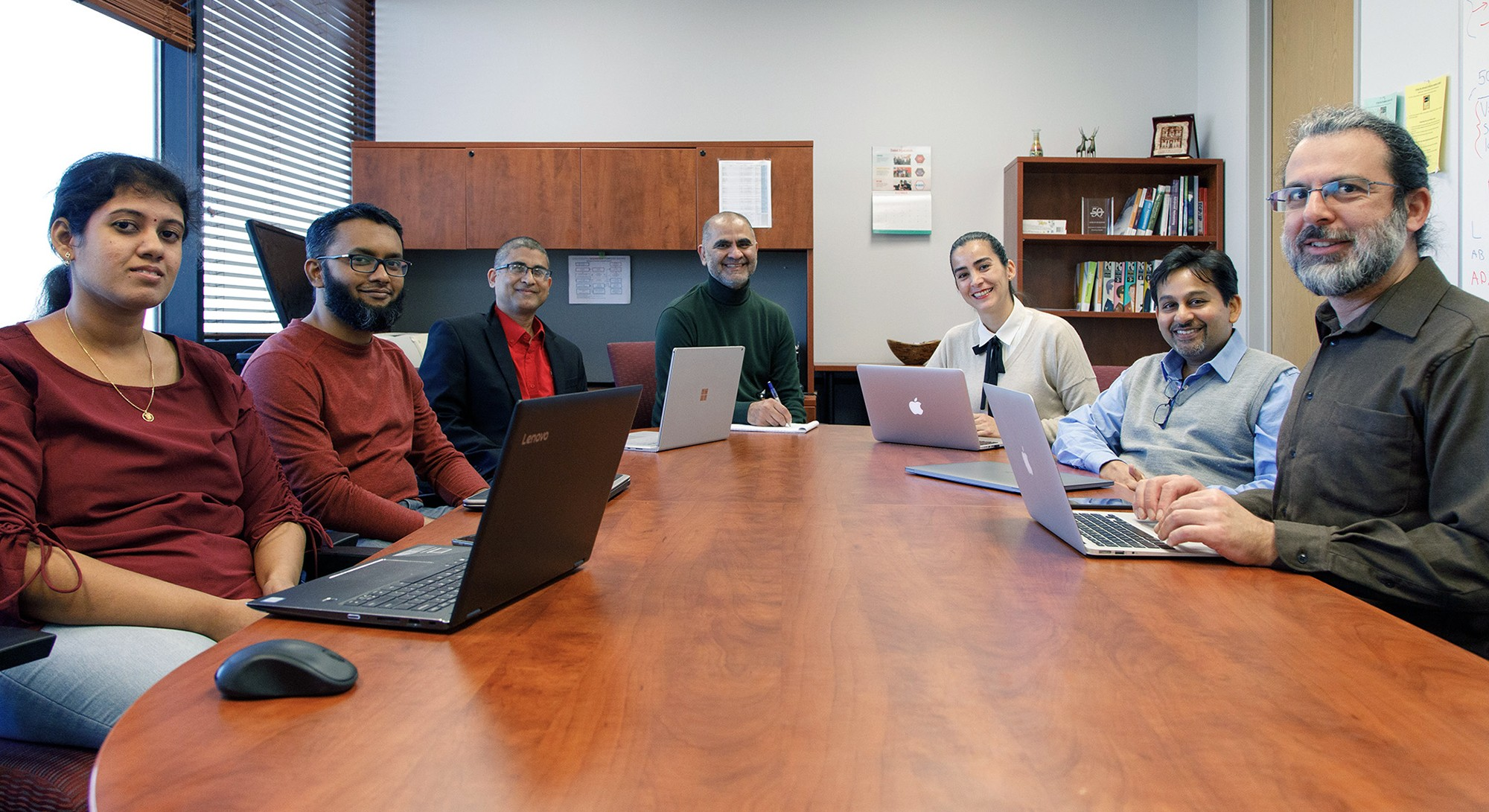 Group of seven people with laptops sitting around conference table