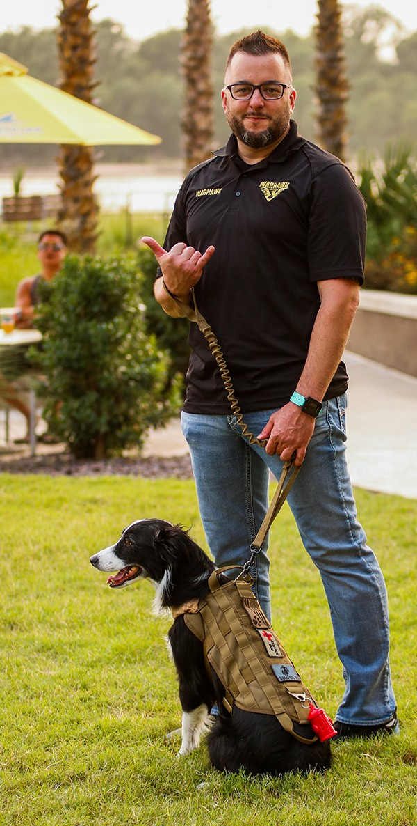 Kevin outdoors, smiling, with service dog on leash sitting in grass