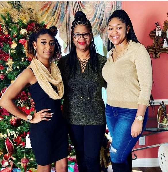 Three women posed inside home with holiday decorations