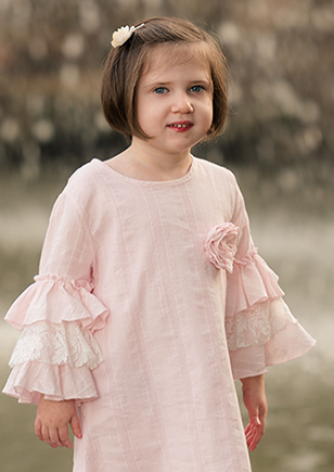 young girl in dress with ruffled sleeves outdoors