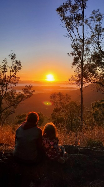 Two people sitting on grounds in wooded area watching vibrant sunset