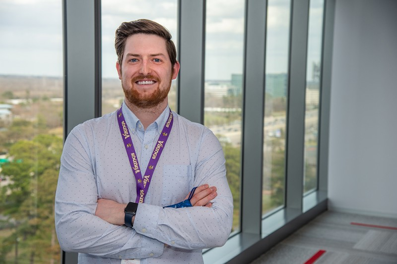 Ryan Cherrey smiling, standing with arms crossed in front of office windows