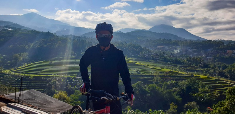 Sani in foreground next to bicycle with a backdrop of green terraces and mountains in distance