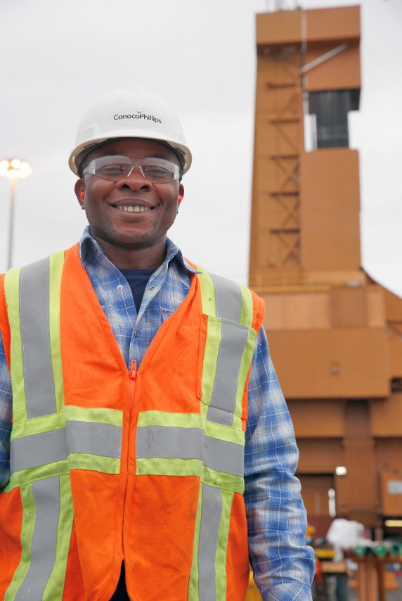 Man wearing safety vest and hard hat smiling with rig in background