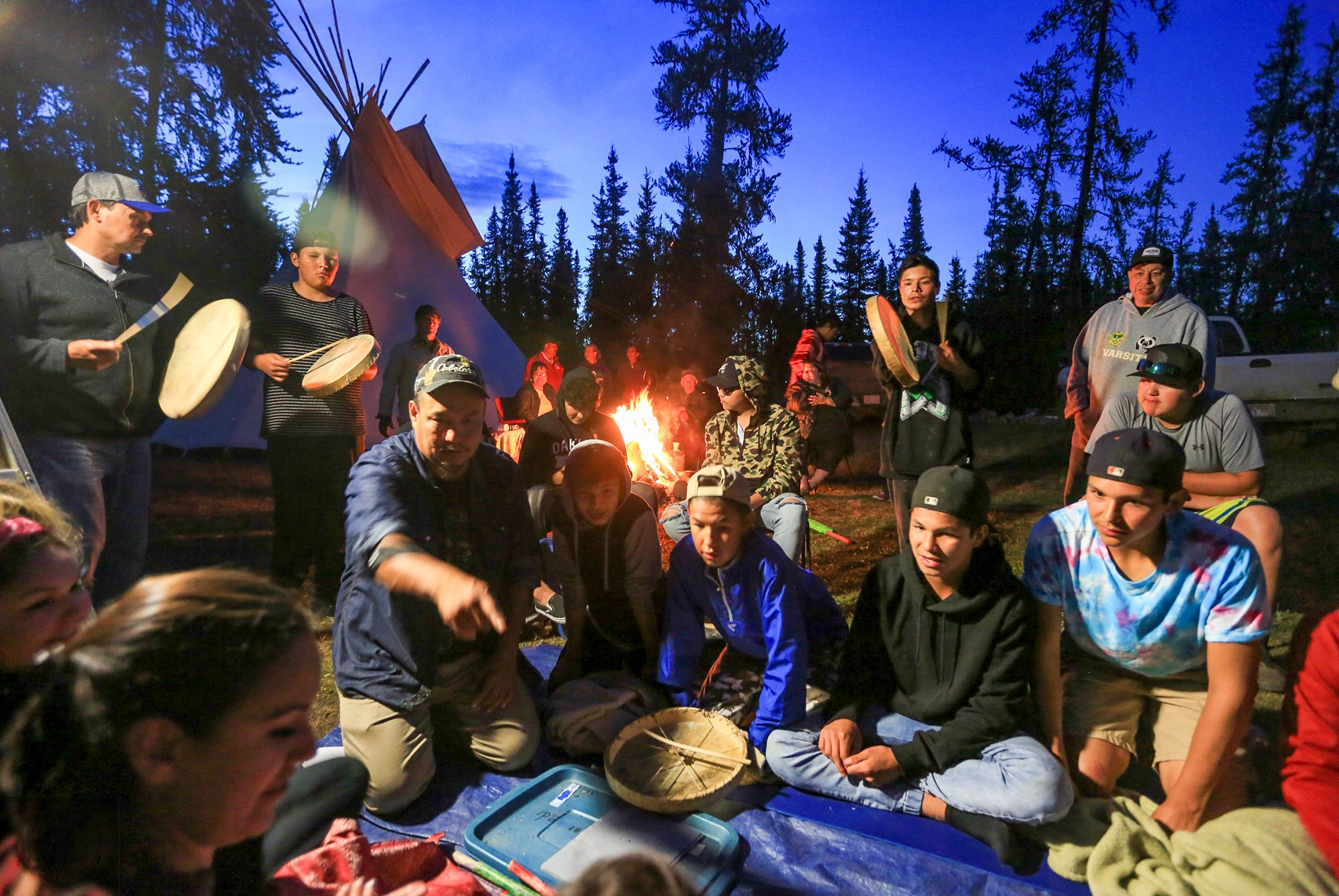 group of people outdoors at night with teepee and campfire in background