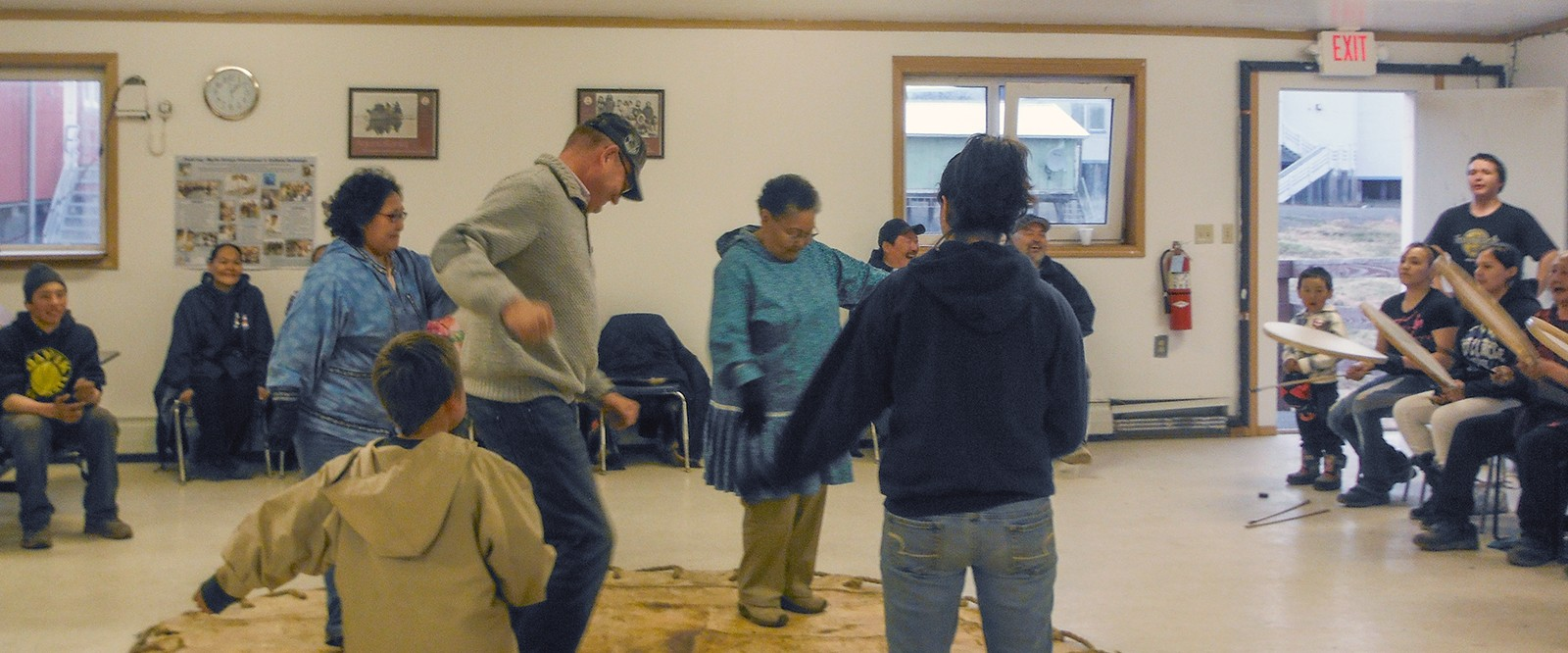 small group of people and spectators in a large room practicing a dance