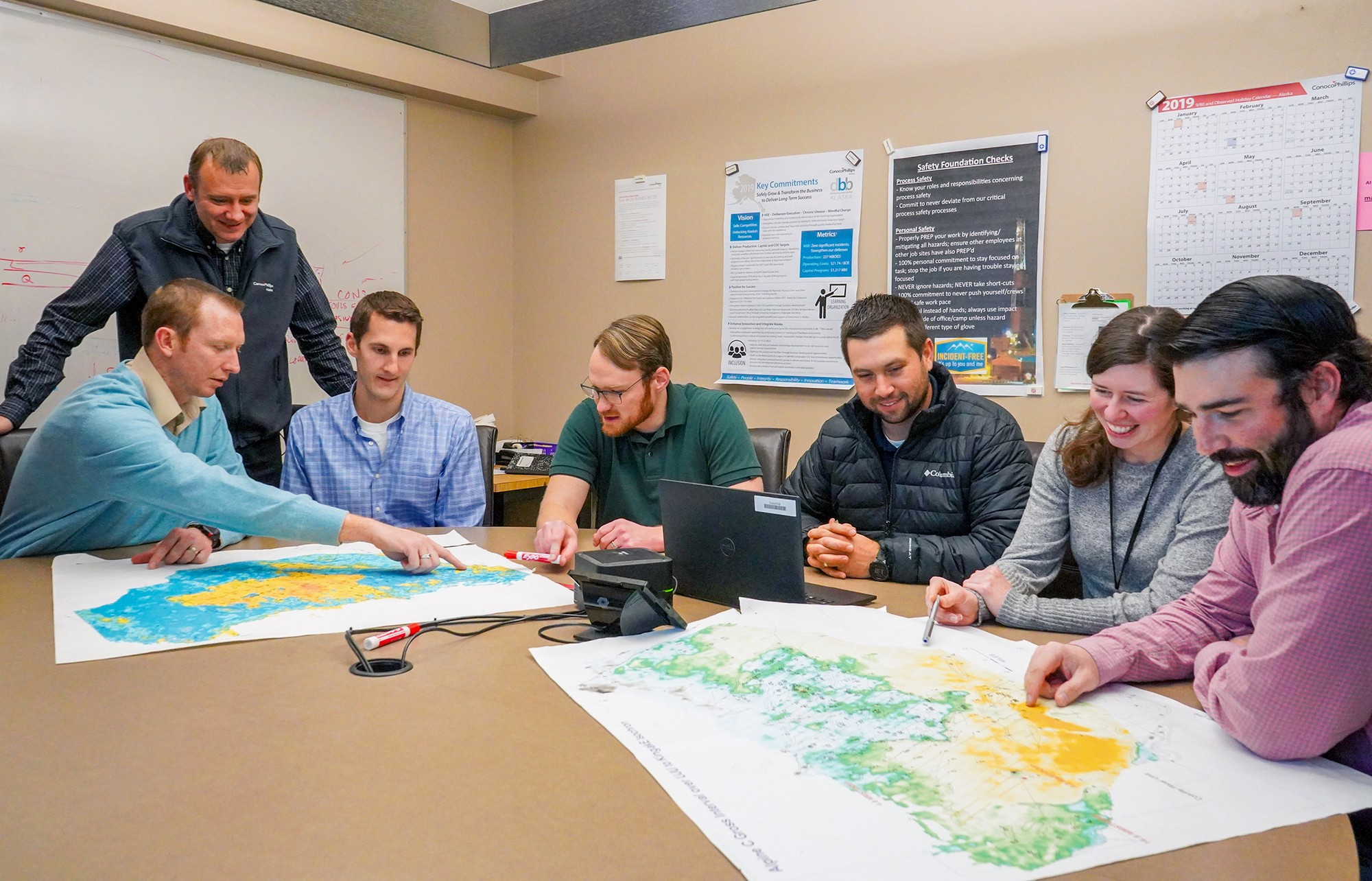 Seven people in conference room looking at maps