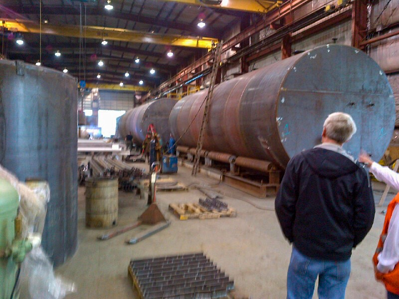 a few people in industrial building with large cylindrical metal objects laying horizontally