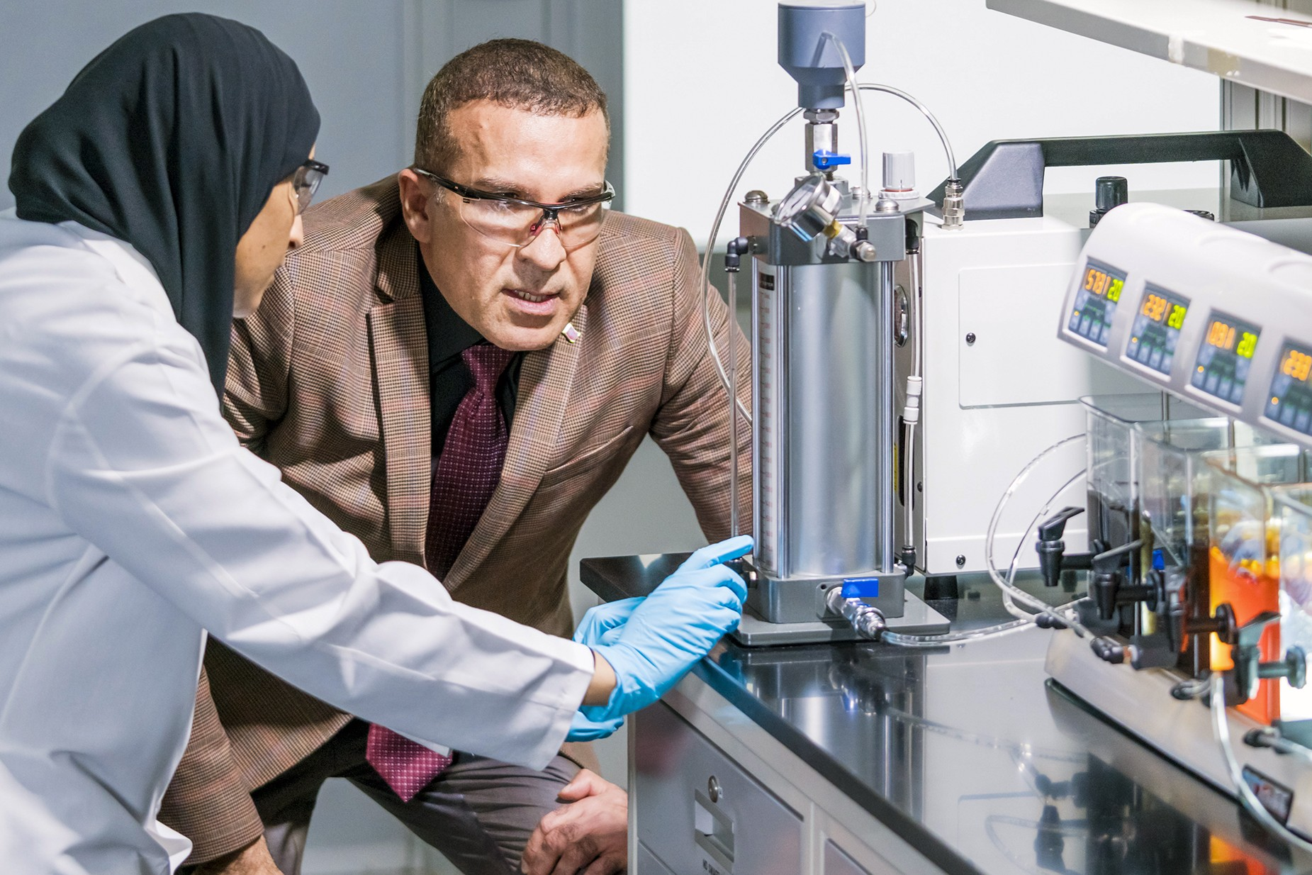 Mashael Al-Maas and Samer Adham looking at testing equipment in laboratory