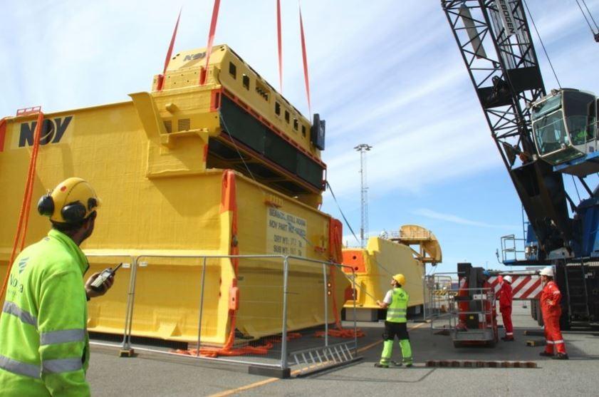 Workers coordinating equipment on deck