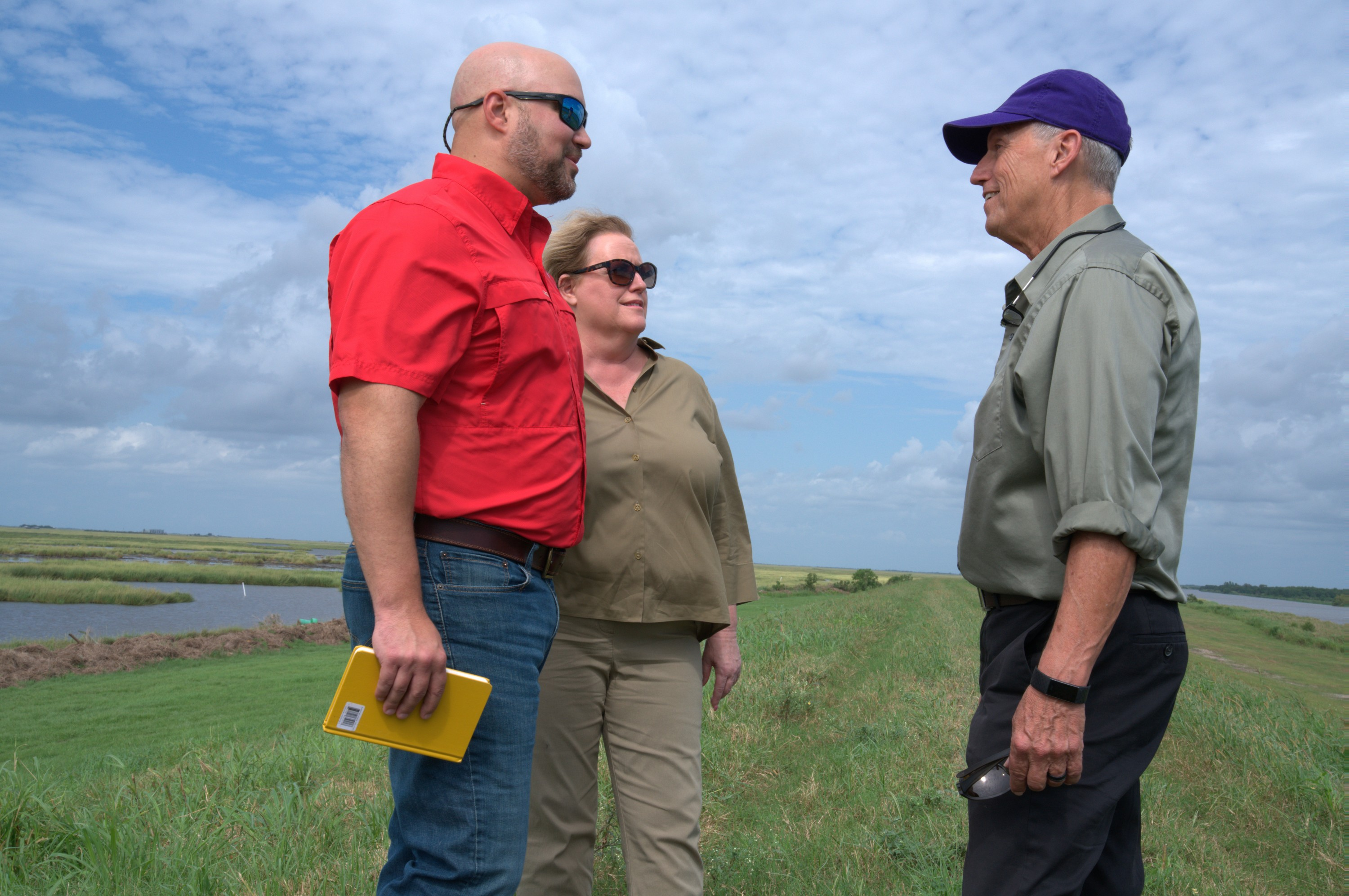Three people talking outside, marshland in background