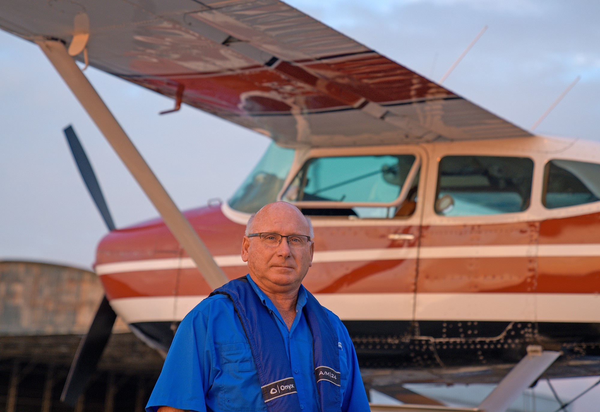 Man in foreground with small plane in background