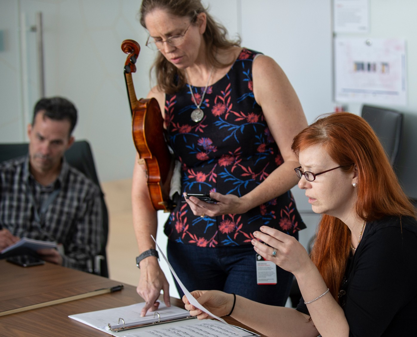 Stephanie standing holding violin, pointing at sheet music, while Bret and Kat are seated at conference table.