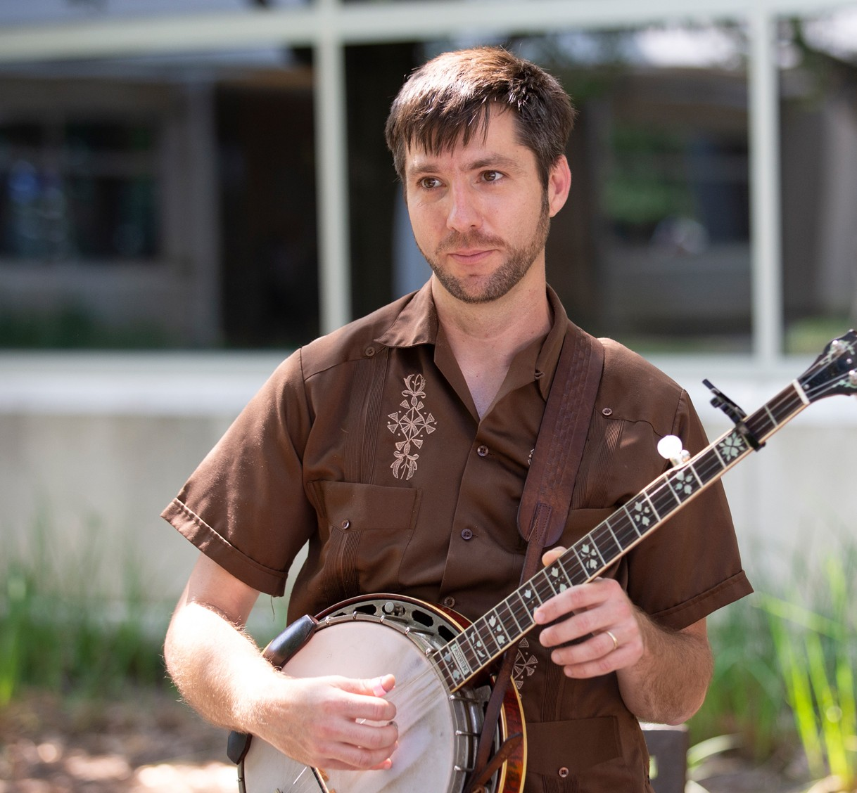 John Templeton outdoors at campus strumming banjo