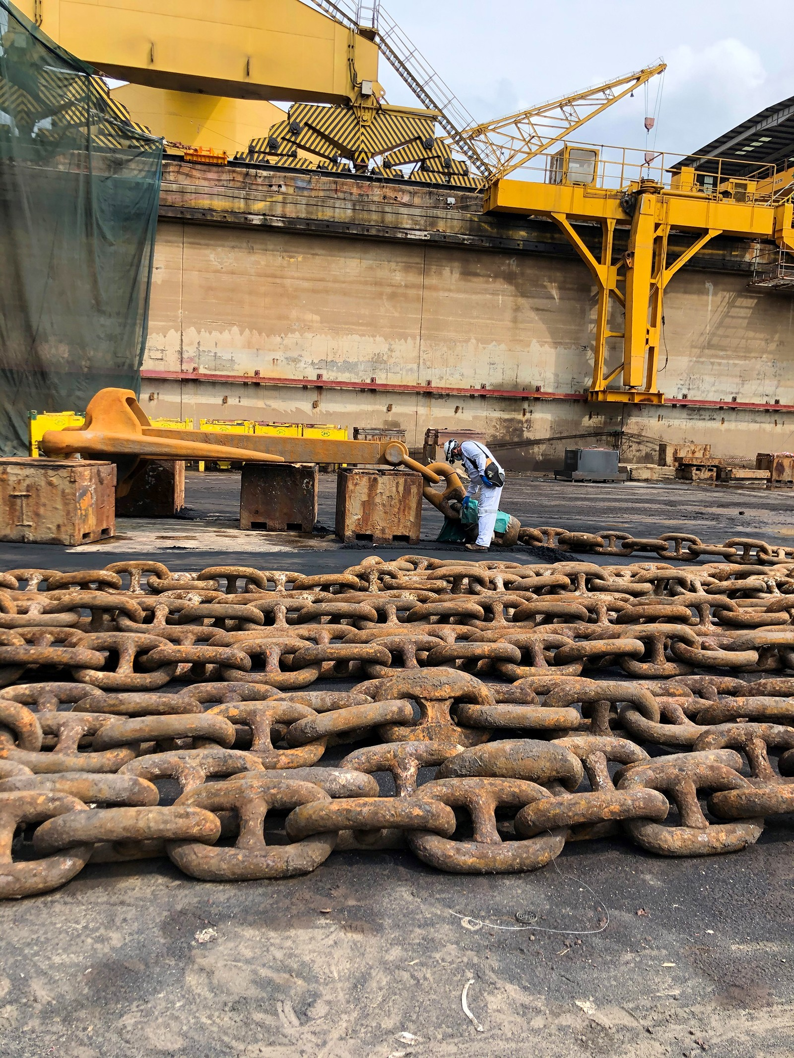 Person examines anchor, which is on blocks on the ships deck. Rows of anchor's large chain in foreground.