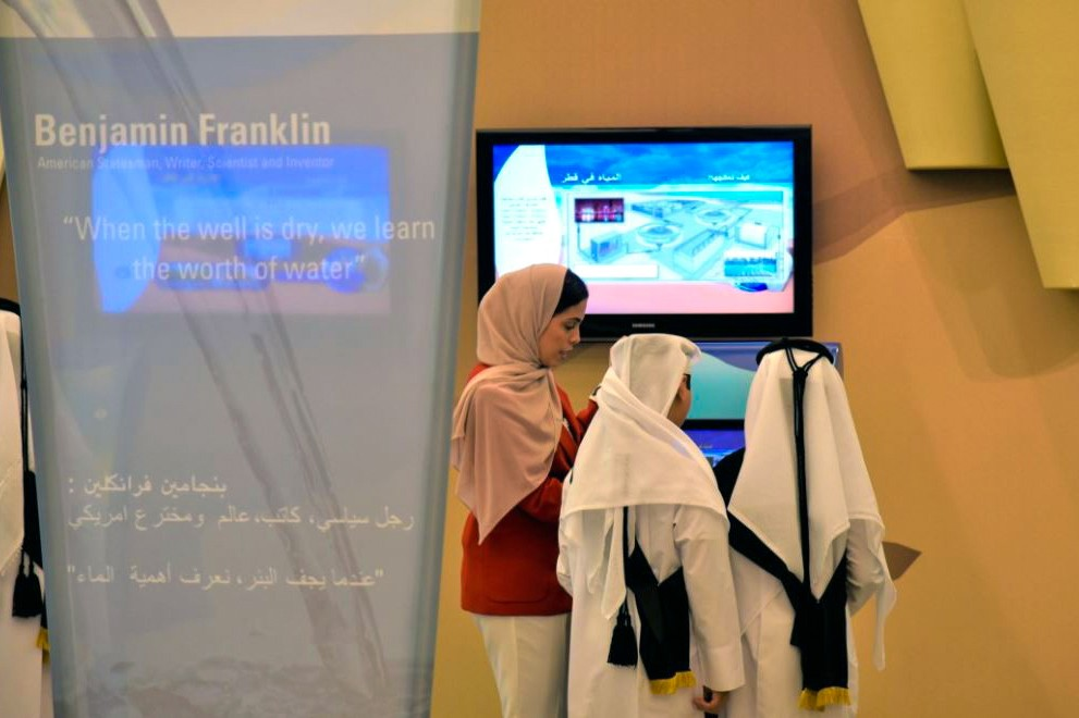 Dareen Dardor with three students looking at interactive displays