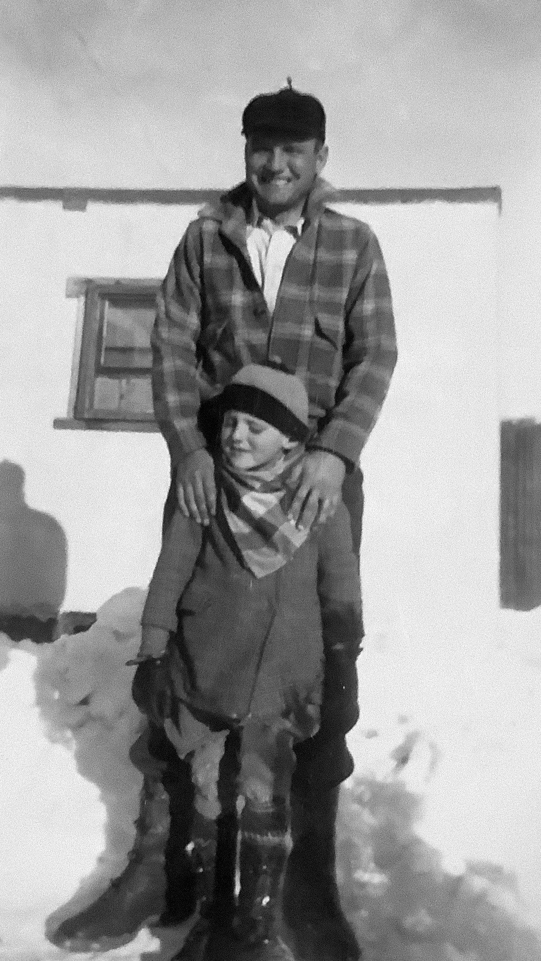 Man smiling with hands on child's shoulders, standing in outdoors with snow pile behind them
