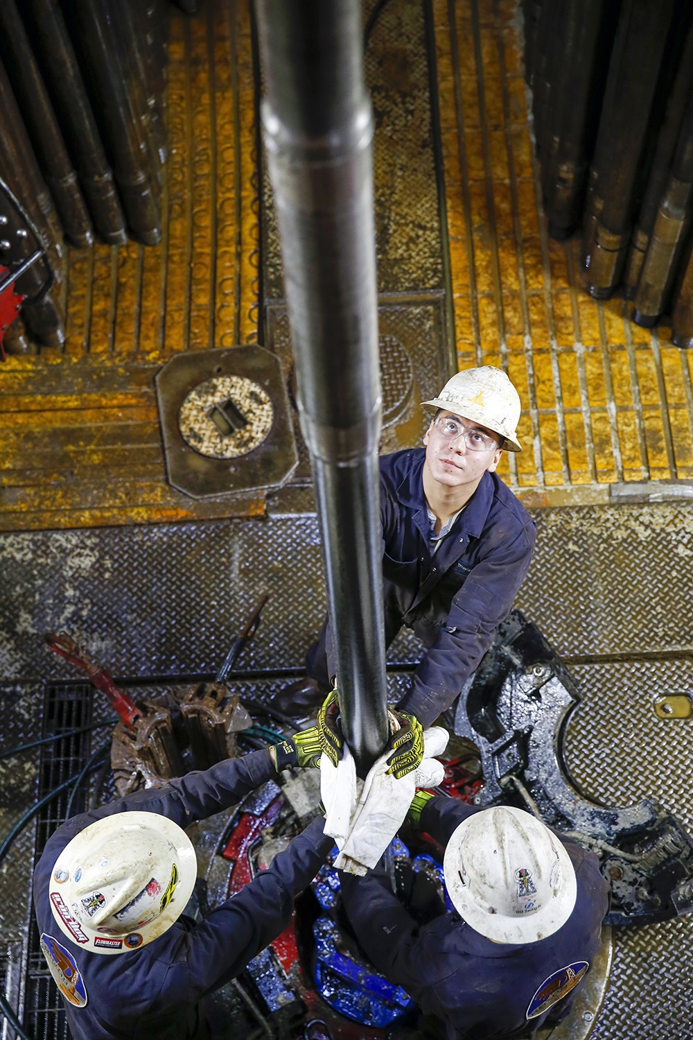 from above, three workers guiding vertical pipe